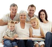 Lächelnde Familie, Fotographienalbum beobachtend Lizenzfreie Stockfotos