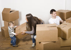 Lächelnde Familie im neuen Haus, das mit Kästen spielt Stockbilder