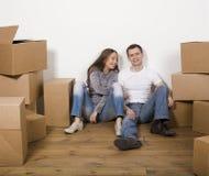 Lächelnde Familie im neuen Haus, das mit Kästen spielt Lizenzfreies Stockfoto