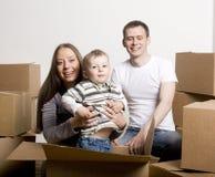 Lächelnde Familie im neuen Haus, das mit Kästen spielt Lizenzfreies Stockbild