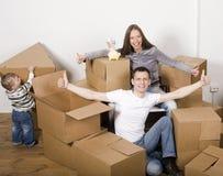 Lächelnde Familie im neuen Haus, das mit Kästen spielt Stockfotografie
