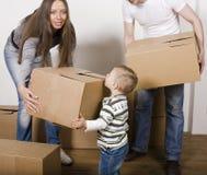 Lächelnde Familie im neuen Haus, das mit Kästen spielt Lizenzfreie Stockfotografie