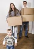 Lächelnde Familie im neuen Haus, das mit Kästen spielt Lizenzfreie Stockbilder