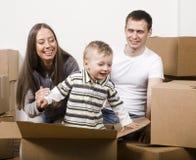 Lächelnde Familie im neuen Haus, das mit Kästen spielt Stockfotos