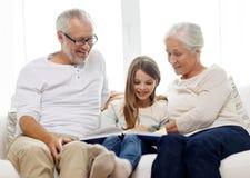 Lächelnde Familie mit Buch zu Hause Stockfoto