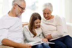 Lächelnde Familie mit Buch zu Hause Stockfotografie