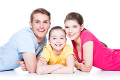 Lächelnde Familie mit dem Kind, das im bunten Hemd sitzt Stockfotografie