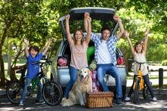 Lächelnde Familie mit den Armen oben Stockfoto