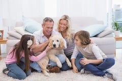 Lächelnde Familie mit ihrem Haustiergelb Labrador auf der Wolldecke stockbild