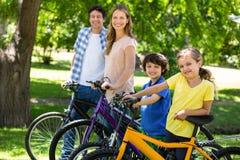 Lächelnde Familie mit ihren Fahrrädern Stockbilder