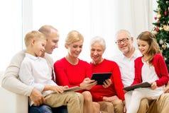 Lächelnde Familie mit Tabletten-PC-Computern zu Hause Stockbild