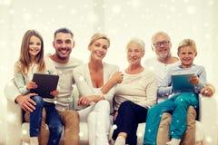 Lächelnde Familie mit Tabletten-PC-Computern zu Hause Stockfotografie