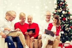 Lächelnde Familie mit Tabletten-PC-Computern zu Hause Lizenzfreies Stockfoto