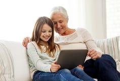 Lächelnde Familie mit Tabletten-PC zu Hause Stockbild