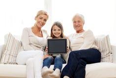 Lächelnde Familie mit Tabletten-PC zu Hause Lizenzfreies Stockfoto