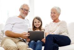 Lächelnde Familie mit Tabletten-PC zu Hause Stockfoto