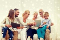 Lächelnde Familie mit Tabletten-PC zu Hause Lizenzfreie Stockfotos