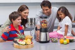 Lächelnde Familie unter Verwendung einer Mischmaschine Stockbilder