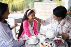 Lächelnde Familie von mehreren Generationen, die zusammen frühstückt stockfotos