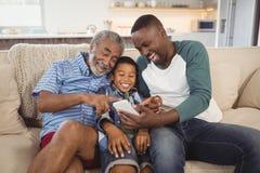 Lächelnde Familie von mehreren Generationen unter Verwendung des Handys im Wohnzimmer Stockfotografie