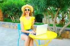 lächelnde Frau arbeitet unter Verwendung einer Laptop-Computers sitzt an einem Café Lizenzfreie Stockfotografie