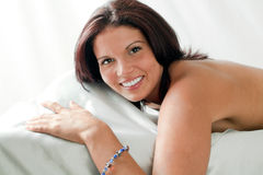 Lächelnde Frau auf Bett mit bloßer Rückseite Stockfotografie