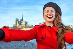 Lächelnde Frau auf Damm in Paris, Frankreich, das selfie nimmt Lizenzfreie Stockbilder