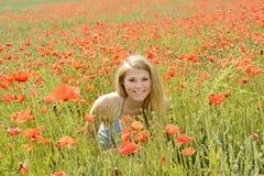 Lächelnde Frau auf dem Mohnblumengebiet Stockbilder