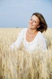 Lächelnde Frau auf dem Weizengebiet stockbild