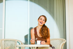 Lächelnde Frau auf der Terrasse, die Tasse Tee isst Lizenzfreie Stockbilder