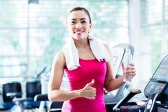 Lächelnde Frau auf der Tretmühle, die Wasserflasche darstellt Stockbild