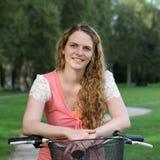 Lächelnde Frau auf ihrem Fahrrad Stockfotografie