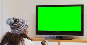 Lächelnde Frau in aufpassendem Fernsehen 4K 4k der warmen Kleidungs stock footage