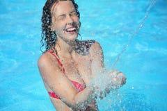 Lächelnde Frau badet im Pool unter Wasser spritzt Lizenzfreies Stockbild