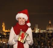 Lächelnde Frau bei Piazzale Michelangelo mit Weihnachtsgeschenk BO Stockfoto