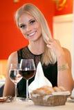 Lächelnde Frau bei Tisch, die Brot und Wein isst Lizenzfreies Stockfoto
