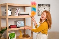 Lächelnde Frau beim Abwischen des Staubes auf hölzernen Regalen Stockbilder
