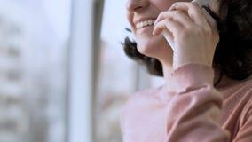 Lächelnde Frau beim Haben des Gespräches über Handy, Fenster am Hintergrund lizenzfreie stockfotografie
