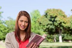 Lächelnde Frau beim voran mit einem Buch in ihrem ha gerade schauen Lizenzfreies Stockfoto