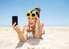 Lächelnde Frau in den Ananasgläsern, die selfie am sandigen Strand nehmen Stockbild