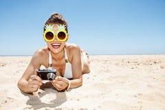 Lächelnde Frau in den Ananasgläsern mit Fotokamera am Strand Lizenzfreie Stockbilder