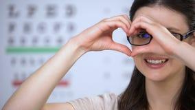 Lächelnde Frau in den Gläsern, die Herz von den Händen, gute Servicequalität, Sorgfalt machen stock video