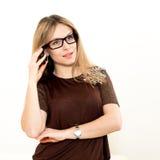 Lächelnde Frau in den Gläsern spricht durch Handy stockfotos