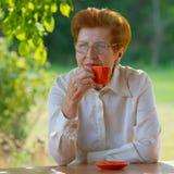 Lächelnde Frau in den Gläsern trinkt Kaffee draußen Stockfotografie