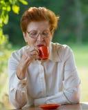 Lächelnde Frau in den Gläsern trinkt Kaffee draußen Lizenzfreie Stockfotos