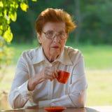 Lächelnde Frau in den Gläsern trinkt Kaffee draußen Stockfoto