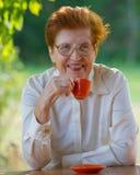 Lächelnde Frau in den Gläsern trinkt Kaffee draußen Stockbilder