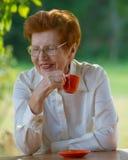 Lächelnde Frau in den Gläsern trinkt Kaffee draußen Lizenzfreies Stockfoto