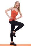 Lächelnde Frau in den Sportkleidungstrainingsbeinen auf einer Matte lizenzfreie stockfotos