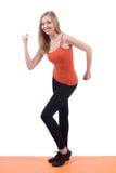 Lächelnde Frau in den Sportkleidungstrainingsbeinen und -händen auf einer Matte lizenzfreies stockfoto